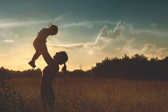Silhouette of a young mother and her little daughter at sunset