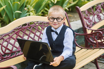 young student with laptop sitting on the bench . The concept of preschool education