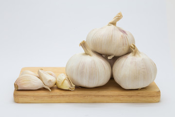 Fresh rood garlic on wooden board, on white background