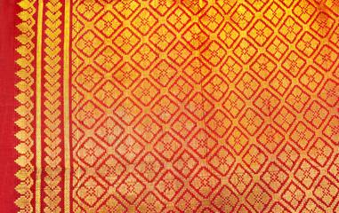 Indian red silk sari with gold floral design.