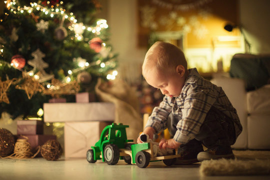 Cute Boy Playing by the Christmas Tree