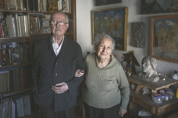 Portrait of old couple standing on artistic studio in home.