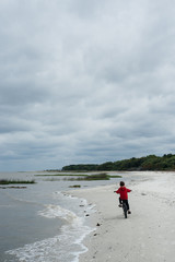 Boy rides his bike on a beach alone