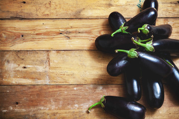Several ripe eggplant lay on boards