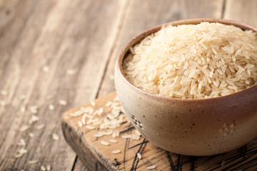 Uncooked parboiled rice in a bowl on wooden table