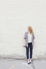 Stylish young woman standing against white brick wall