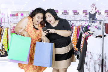Two women using a smartphone in the mall