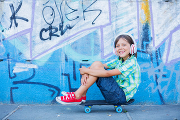 Cute boy with skateboard outdoors, standing on the street with different colorful graffiti on the walls