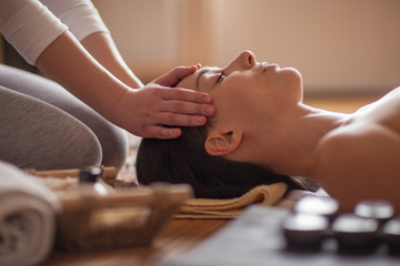 Young Woman Enjoying Head Massage in Spa Center