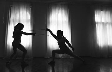 Two women fencing in studio