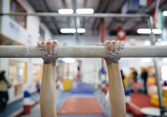 Child practices on the parallel bars in a gymnastics gym