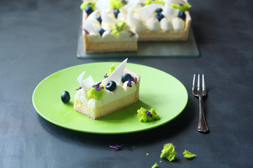 Piece of  Lemon Tart with Cream Cheese and Blueberries decorated with pieces of Sponge Moss Cake, on green plate, on dark background.