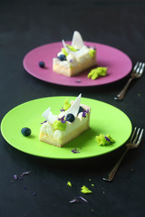 Two Pieces of  Lemon Tart with Cream Cheese and Blueberries decorated with pieces of Sponge Moss Cake, on green and purple plates, on dark background.