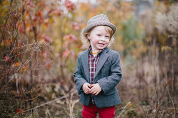 Portrait of a cute boy in a blazer wearing a fedora hat