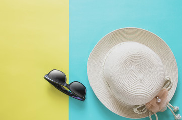 Summer holiday minimal background concept. Straw hat, sunglasses on yellow and blue background.