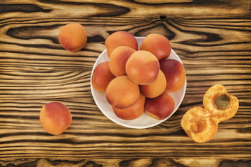 On the table and on a white saucer lie ripe apricots