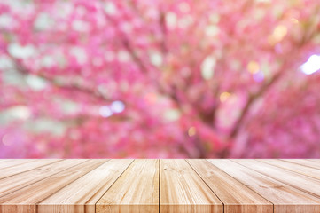 Empty wooden table top with blurred pink cherry or cherry blossom background.