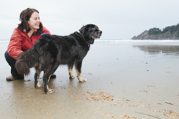 Young woman playing with her pet black dog on the beach