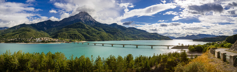Panoramic view of Serre-Poncon Lake with Savines-le-Lac and its bridge with the Grand Morgon mountain peak in summer. Hautes-Alpes, Durance Valley, PACA Region, Southern French Alps, France