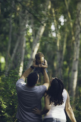 Mom and dad playing with their son in the forest