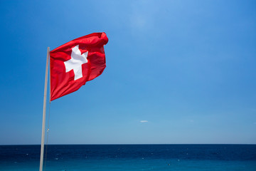 A swiss flag floating in the wind over the sea.