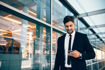 Business executive with mobile phone at airport