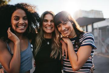 Three young women having fun on city street