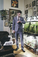 Portrait of a Man in Suit at Home in his Living Room next to Fish Tank