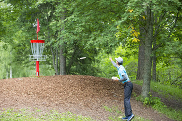 Professional disc golf athlete is throwing the disc in to the basket outdoors.