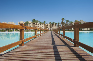 Large swimming pool with wooden bridge at luxury tropical hotel