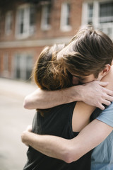 Affectionate young couple hugging outdoors