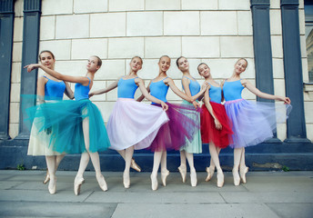 Ballet dancers dancing on street. Young ballerinas in color tutus full length
