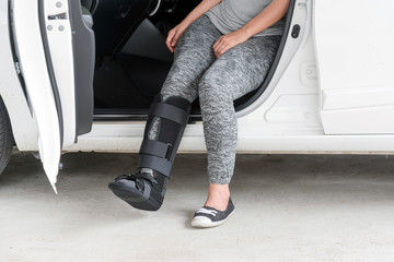 injured woman wearing sportsware with black cast on leg  sitting in white car, insurance concept