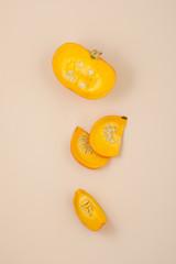 Fresh orange cut pumpkin on a light beige pastel background..