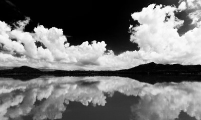 White clouds against the black sky are reflected in the lake.