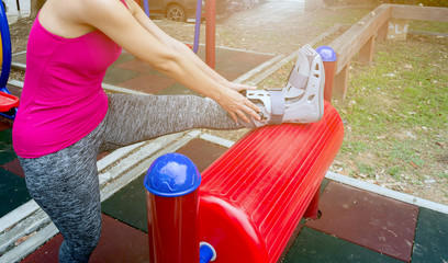injured woman wearing sportswear  broken ankle wearing ankle support on exercise equipment in a public park background, health care concept