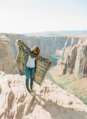 young woman holding up blanket overlooking canyon