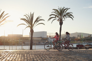 Two young girls riding a bike by the seaport of Barcelona city