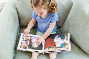 Toddler looking through a photo album while sitting in a big chair