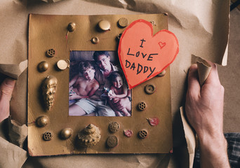 Opening Father's Day Gift: Faded Photo in Childs Frame