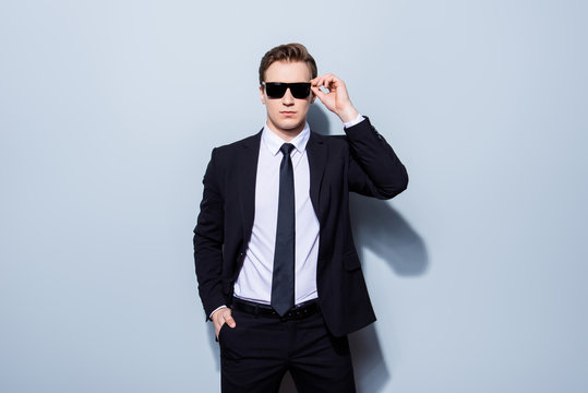 Harsh agent, standing on a pure background. He looks stunning and severe, wearing suit and sunglasses, fixing them and has a hand in a pocket