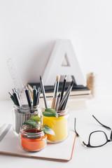 Diy pencil holder jars on a cute white home desk.