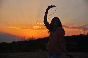 Silhouette of Young Attractive Hipster Girl Listening Music On The Mobile Phone And Dance At Sunset