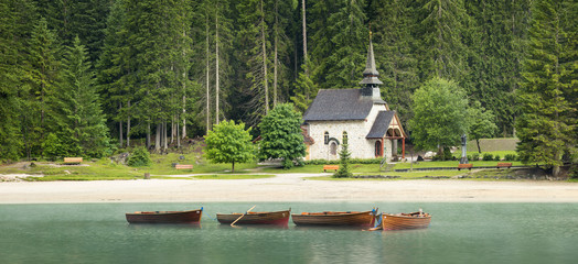 Old church and boats on the lake in Italy