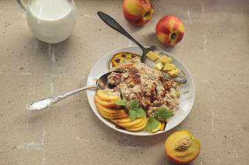 Breakfast from oatmeal porridge nectarine and milk cutlery