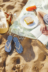 Sleepping young woman with a book on the beach.