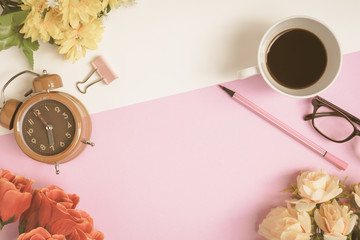 Flat lay coffee glasses and clock with pens and flowers