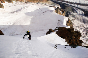 single male mountain climber free solo on a steep north face in the Swiss Alps near Zermatt