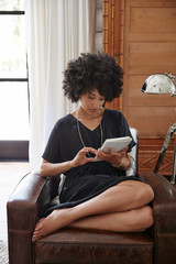 African American woman working on tablet in bedroom