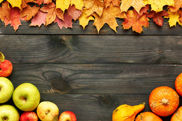 Autumn leaves, apples and pumpkins over wooden background